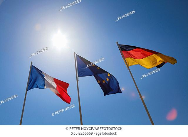 French, German and European flags against sun and blue sky