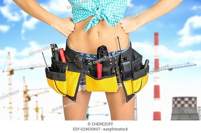 Woman in tool belt with different tools. Hands on hip. Cropped image. Tower cranes and chimneys on background