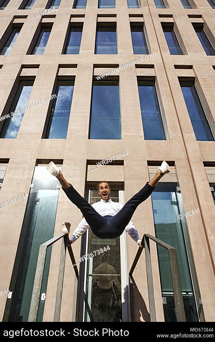 Happy entrepreneur dancing against building