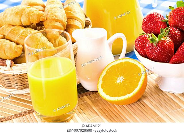 orange juice, croissants and strawberries still life