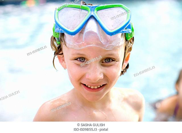 Portrait of boy with swimming goggles on head in outdoor swimming pool