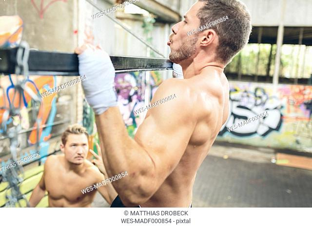 Young man doing chin-ups supported by training partner