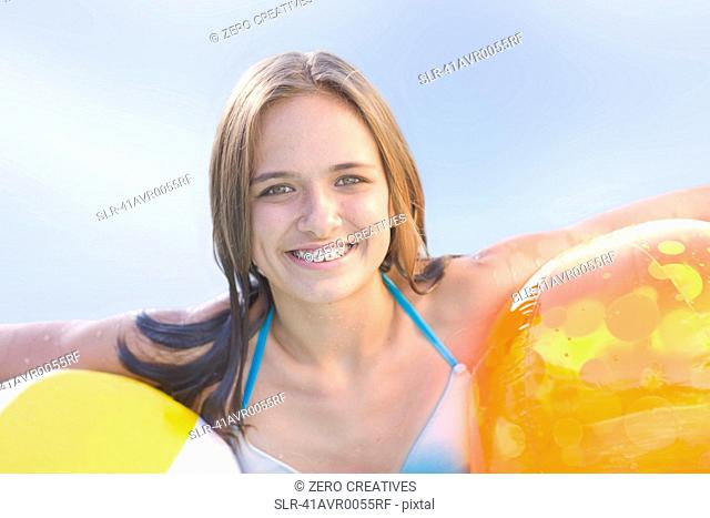 Teenage girl in braces holding toys