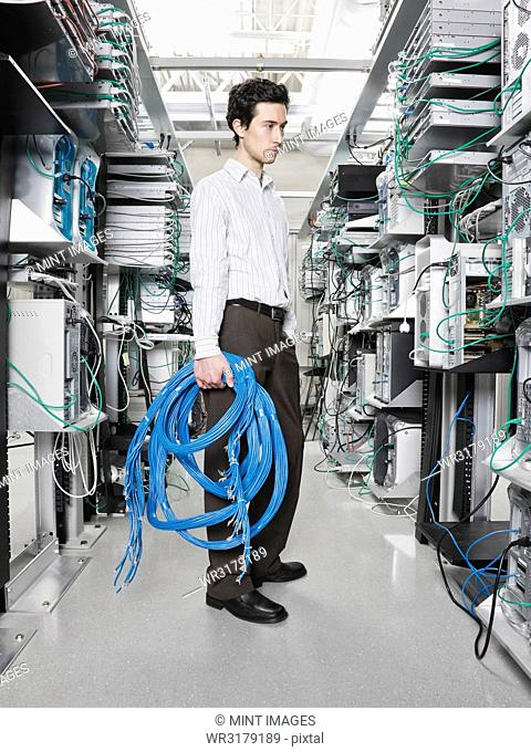Male computer technician holding CAT 5 cables and standing in the aisle of a computer server farm