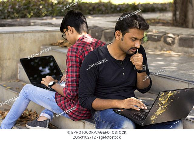 Young students using laptop and smartphone lean on each other back to back on strairs in park