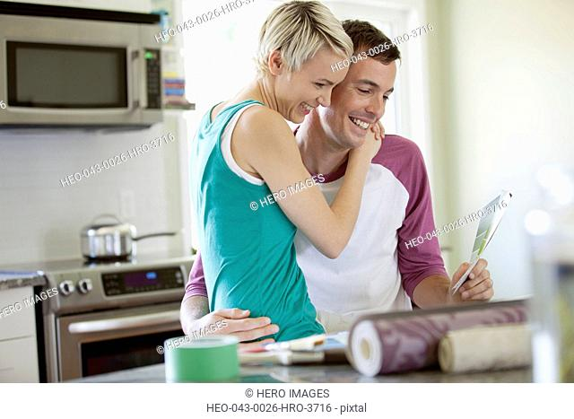 mid adult couple being affectionate in the kitchen