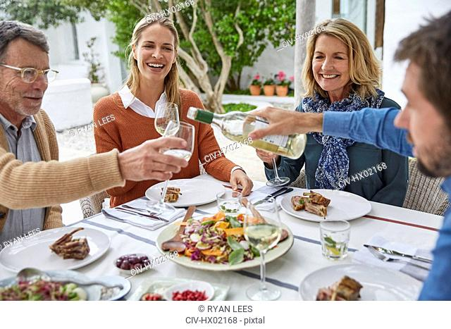 Couples drinking white wine and eating lunch on patio