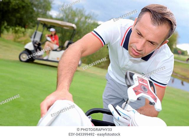 Man leaning towards golfing bag