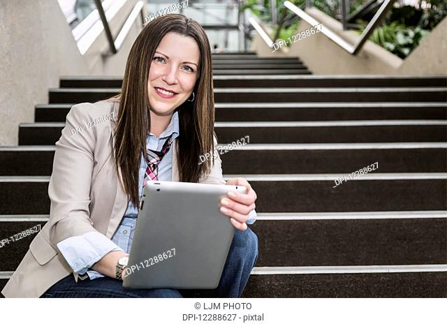 Portrait of a mature business woman sitting on stairway in the atrium of an office building with a tablet; Edmonton, Alberta, Canada