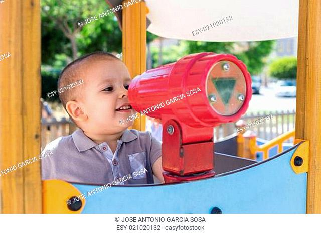 A toddler looking through a toy telescope in a playground