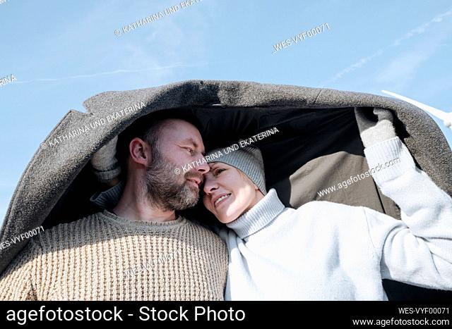 Portrait of mature couple hiding under coat