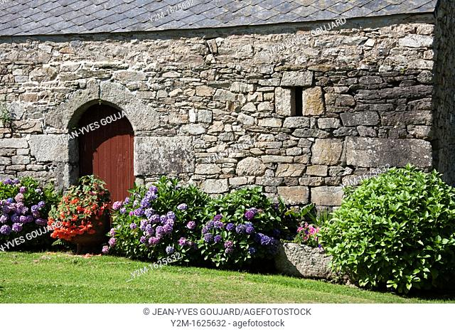 Old stone wall, doors and flower garden, Brittany, France