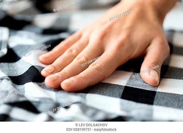 laundry, clothes, fashion and people concept - close up of hand with checkered clothing item