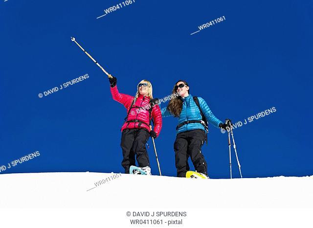 Two friends having fun snowshoeing