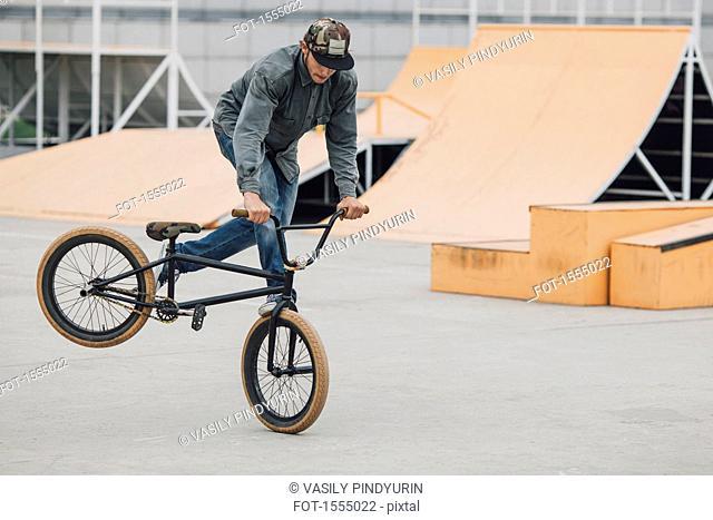 Teenager performing wheelie with bicycle at skateboard park