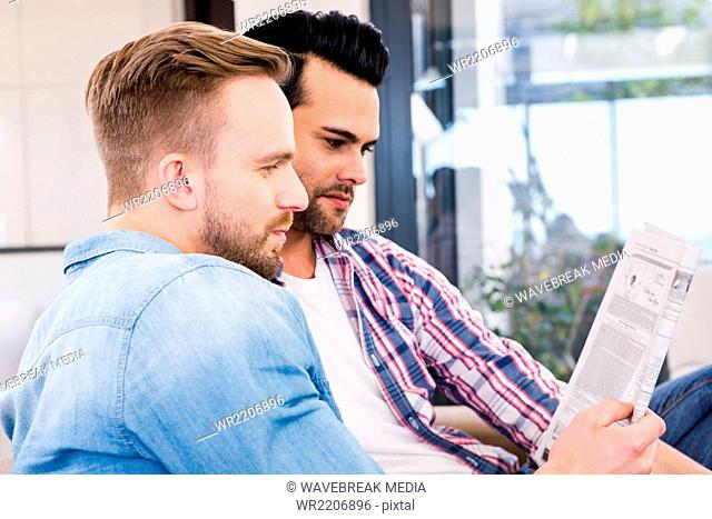 Gay couple relaxing on the couch reading newspaper