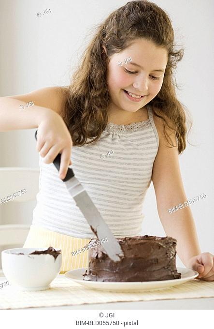 Hispanic girl icing cake