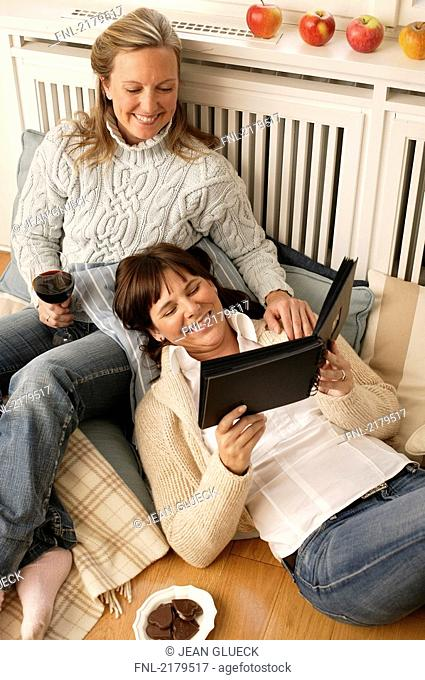 High angle view of woman and her daughter looking at photo album and smiling