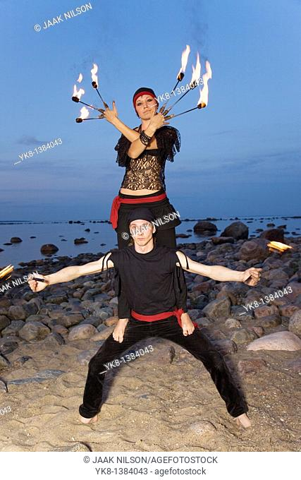 Woman and Man Fire Dancers in Costume Juggling Torches by Water