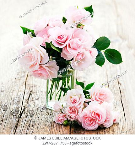 Delicate pale pink Roses in a glass jar on weathered wooden table