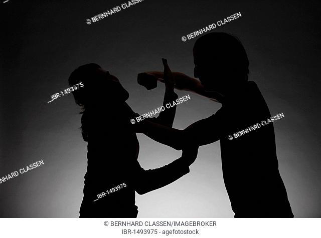 Silhouette of a man beating a woman, symbolic image for domestic violence and abuse