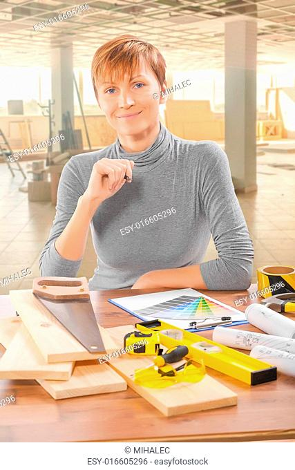 female worker sitting at table with tools