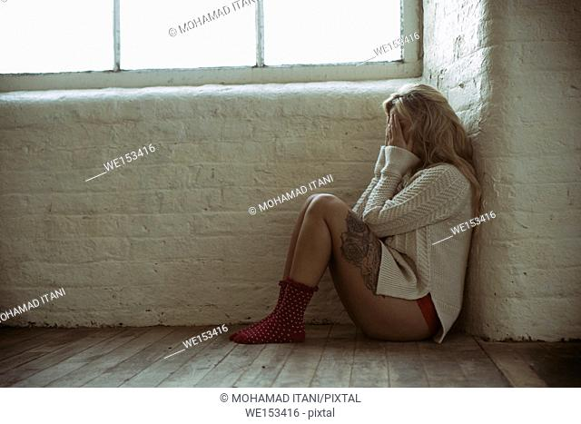 Sad young woman wearing knickers and wool jumper sitting on the floor by the window hiding face with hands crying