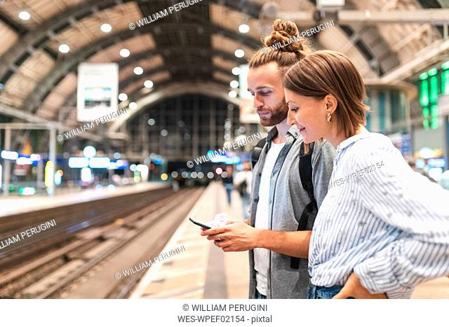 Young couple waiting for the train at the station and using smartphone, Berlin, Germany