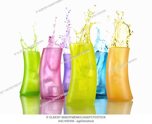 Colorful bursting drink splashing in multicolor glasses Isolated on whitye background