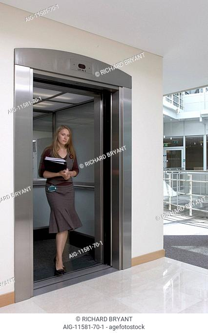 Office life and interiors part two. Woman stepping out of lift