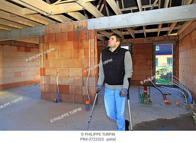 France, young working person with crutches in a house in construction