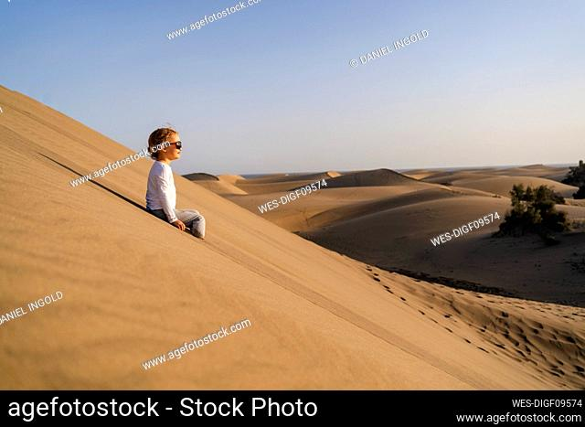 Girl sitting in sand dunes, Gran Canaria, Spain
