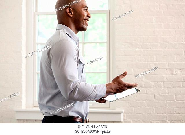 Mid adult office worker holding digital tablet and smiling
