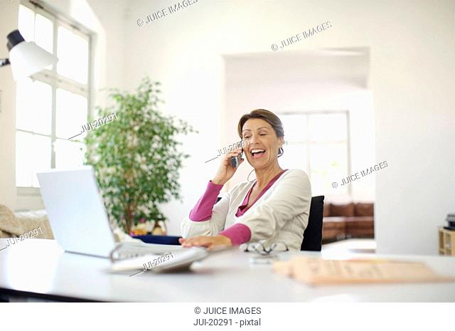 Happy mature woman on the phone at home office