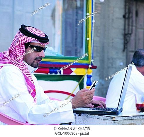 Saudi man using laptop and mobile phone in Old Town of Jeddah, Saudi Arabia