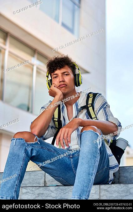 Boring young afro with headphones on sitting on the street
