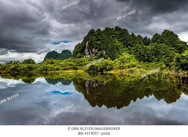 Karst hills with dark clouds, view of the landscape, reflection in the water, near Hpa-an, Karen or Kayin State, Myanmar, Burma