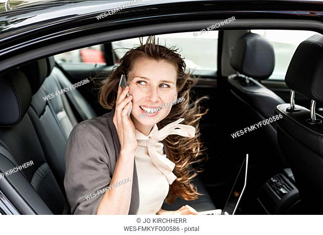 Germany, portrait of smiling businesswoman sitting in a car telephoning with smartphone