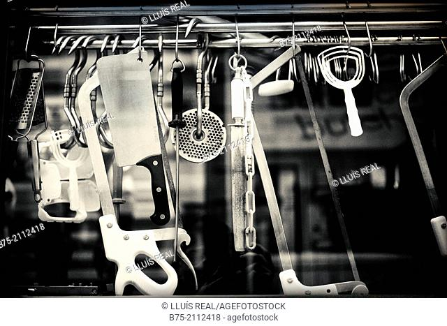 Utensils in a butcher viewed through a glass from the street in London, England, UK, Europe