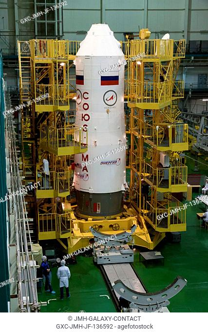 With the Soyuz TMA-10M spacecraft nestled inside, the third stage of a Soyuz booster rocket stands erect in the Integration Facility at the Baikonur Cosmodrome...
