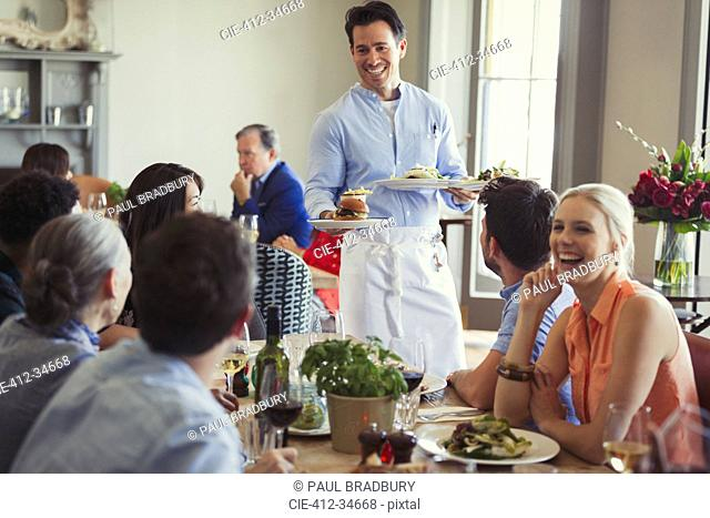 Smiling waiter serving food to friends dining at restaurant table