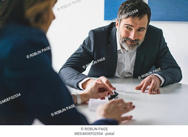 Businessman and businesswoman playing table football in office