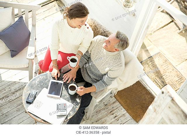 View from above mature couple drinking coffee and using digital tablet on sun porch