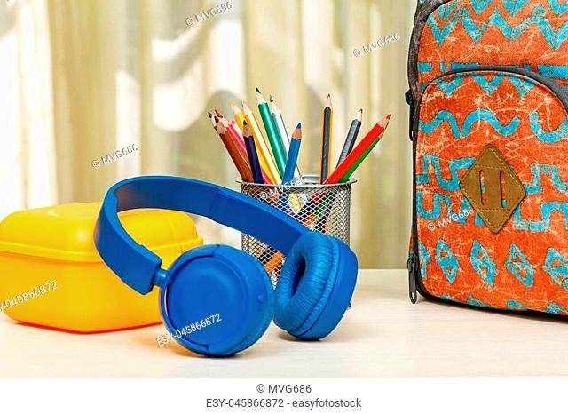 School backpack with school supplies. Metal stand for pencils with color pencils, yellow sandwich box and headphones on wooden table