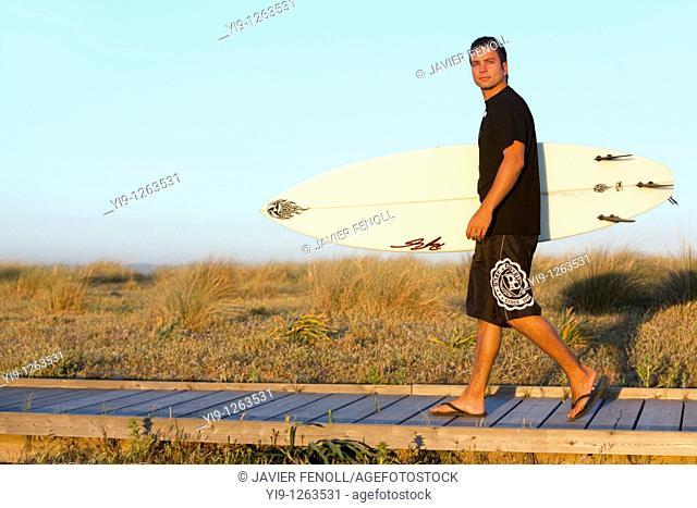 Side view of man walking along ocean carrying surf board