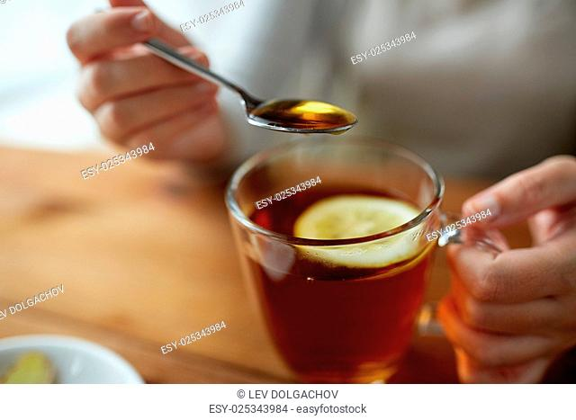 healthy food, eating and ethnoscience concept - close up of woman adding honey to tea cup with lemon