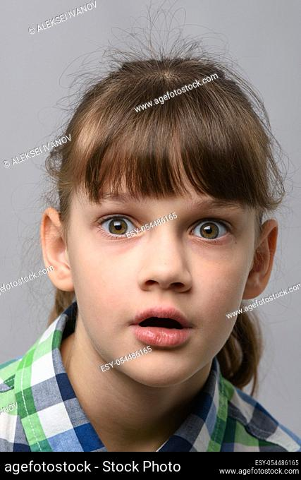 Portrait of a very surprised ten year old girl with bulging eyes and open mouth, European appearance, close-up