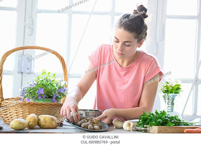 Young woman preparing snails at kitchen counter, Vogogna,Verbania, Piemonte, Italy
