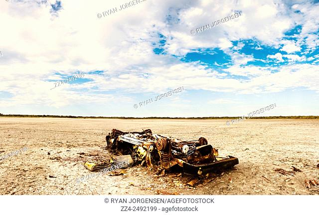 Large format three image photo stitch of an abandoned burnt out car wreck laying upside down on a dry barren outback Australia landscape, taken Deception Bay