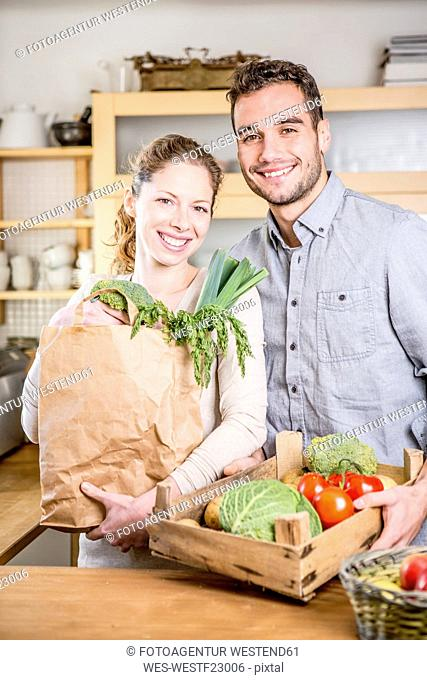 Smiling couple with box of vegetables in kitchen